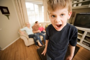 Young boy looking angry in living room